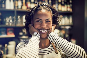 Smiling young African female entrepreneur standing in her cafe