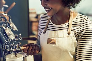 Smiling young African barista making fresh coffee in a cafe