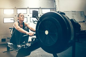 Fit woman exercising on a rowing machine at the gym