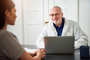 Senior doctor talking to young woman in clinic