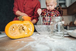 Dad and son cuts a pumpkin for a pie
