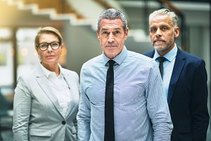 Confident mature businessman standing with colleagues in an office