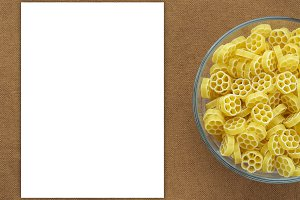 Macaroni ruote Pasta in a glass cup on a brown suburban background texture with a side. Close-up with the top. White space for text and ideas.
