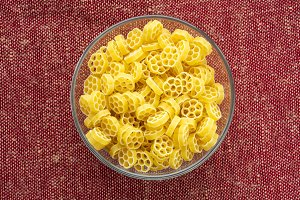 Macaroni ruote pasta in a glass bowl on a red brown rustic texture background, in the center close-up from the top.