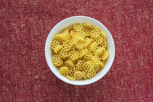 Macaroni ruote pasta in a white cup on a red brown rustic texture background, in the center close-up from the top.
