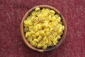 Macaroni ruote pasta in a wooden bowl on a red brown rustic texture background, in the center close-up from the top.