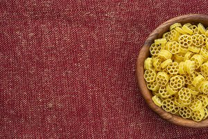 Macaroni ruote pasta in a wooden bowl on a red brown rustic texture background with a side. Close-up from the top Free space for text.