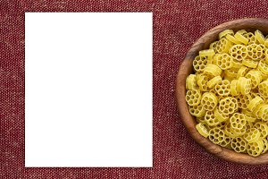 Macaroni ruote pasta in a wooden bowl on a red brown rustic texture background with a side. Close-up from the top. White space for text and ideas.