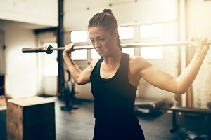 Fit young woman exercising with a barbell in a gym