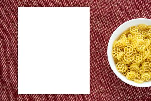 Macaroni ruote pasta in a white bowl on a red brown rustic texture background with a side. Close-up from the top. White space for text and ideas.