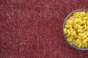 Macaroni ruote pasta in a glass bowl on a red brown rustic background texture with a side. Close-up with the top. Free space for text.
