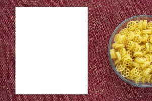 Macaroni ruote pasta in a glass bowl on a red brown rustic background texture with a side. Close-up with the top. White space for text and ideas.