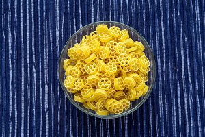 Macaroni ruote pasta in a glass bowl on a striped white blue fabric background in the center. Close-up with the top.