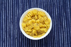 Macaroni ruote Pasta in a white cup on a striped white blue cloth background in the center. Close-up with the top.