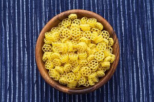 Macaroni ruote pasta in a wooden bowl on a striped white blue cloth background in the center. Close-up with the top.