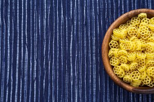 Macaroni ruote pasta in a wooden bowl on a striped white blue cloth background with a side. Close-up with the top. Free space for text.