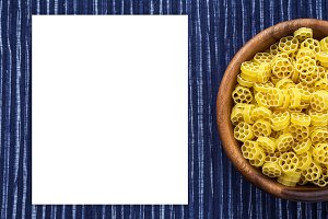 Macaroni ruote pasta in a wooden bowl on a striped white blue cloth background with a side. Close-up with the top. White space for text and ideas.