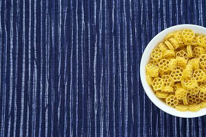 Macaroni ruote pasta in a white bowl on a striped white blue cloth background with a side. Close-up with the top. Free space for text.