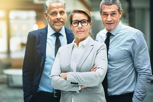 Confident mature businesswoman standing with coworkers in an office