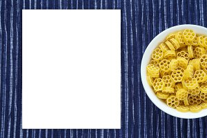 Macaroni ruote pasta in a white bowl on a striped white blue cloth background with a side. Close-up with the top. White space for text and ideas.
