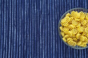Macaroni ruote Pasta in a glass cup on a striped white blue cloth background with a side. Close-up with the top. Free space for text.