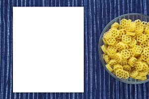 Macaroni ruote Pasta in a glass cup on a striped white blue cloth background with a side. Close-up with the top. White space for text and ideas.