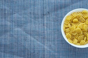 Macaroni ruote pasta in a white bowl on a blue knitted textured background with a side. Close-up with the top. Free space for text.