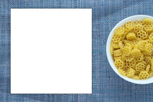 Macaroni ruote pasta in a white bowl on a blue knitted textured background with a side. Close-up with the top. White space for text and ideas.