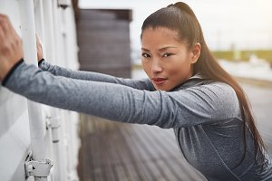 Young Asian woman in sportswear stretching outdoors before a run