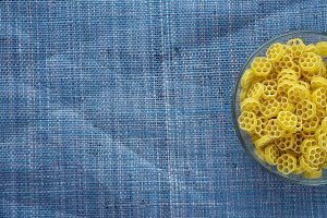 Macaroni ruote Pasta in glass cup on blue knitted textured background with side. Close-up with the top. Free space for text.