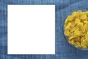 Macaroni ruote Pasta in glass cup on blue knitted textured background with side. Close-up with the top. White space for text and ideas.