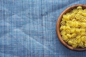 Macaroni ruote pasta in wooden bowl on blue knitted textured background with side. Close-up with the top. Free space for text.