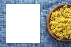 Macaroni ruote pasta in wooden bowl on blue knitted textured background with side. Close-up with the top. White space for text and ideas.