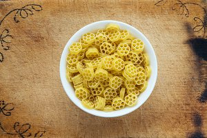 Macaroni ruote pasta in a white cup on a wooden cutting board, textured background, in the center close-up from the top.