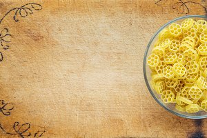 Macaroni ruote pasta in a glass cup on a cutting wooden board, textured background with a side. Close-up with the top. Free space for text.