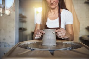 Artisan creatively shaping clay in her ceramic studio