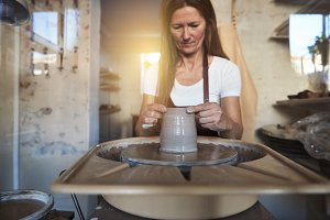 Female artisan creatively shaping clay in her ceramic studio
