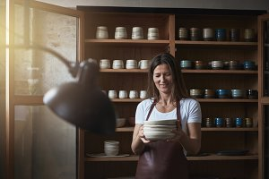 Smiling artisan standing with plates in her creative pottery gallery