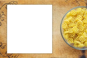 Macaroni ruote pasta in a glass cup on a cutting wooden board, textured background with a side. Close-up with the top. White space for text and ideas.