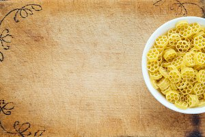 Macaroni ruote pasta in a white bowl on a cutting wooden board, textured background with a side. Close-up with the top. Free space for text.