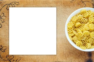 Macaroni ruote pasta in a white bowl on a cutting wooden board, textured background with a side. Close-up with the top. White space for text and ideas.