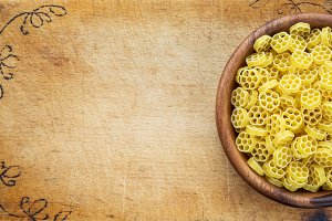 Macaroni ruote pasta in a wooden bowl on a cutting wooden board, texture background with a side. Close-up with the top. Free space for text.