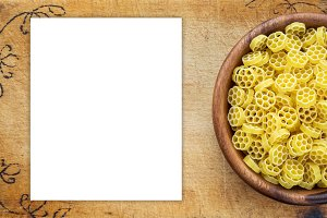 Macaroni ruote pasta in a wooden bowl on a cutting wooden board, texture background with a side. Close-up with the top. White space for text and ideas.