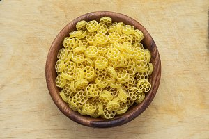 Macaroni ruote pasta in a wooden bowl on a wooden table texture background, in the center close-up with the top.