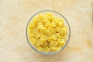 Macaroni ruote pasta in a glass bowl on a wooden table texture background, in the center close-up with the top.