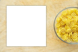 Macaroni ruote Pasta in a glass cup on a wooden table textured background with a side. Close-up with the top. White space for text and ideas.