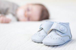 Baby blue leather shoes over a bed