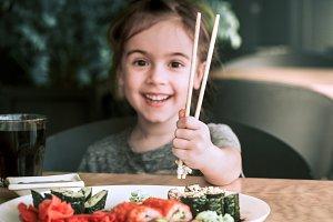 Little girl is eating sushi