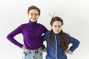 Studio shot of two brunette sisters posing against white wall background: elderly girl smiling broadly making gesture, holding two fingers behind her angry sister's head for horns or rabbit ears