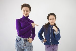 Human facial expressions, emotions and body language. Picture of serious 12 year old girl pointing at herself while her positive smiling elderly sister indicating finger in her direction either